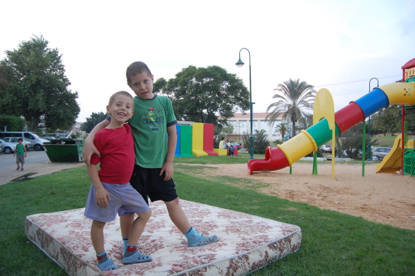 Lads playing in a Sderot playground, in front of the bomb shelter.